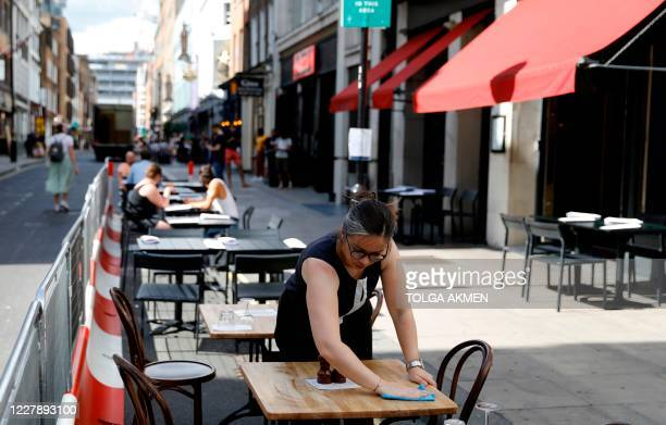 """Restaurant worker cleans an empty table outside a restaurant in London on August 3 as the Government's """"Eat out to Help out"""" coronavirus scheme to..."""