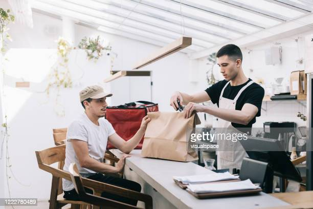 restaurant worker handing over take out food to delivery guy - packaging stock pictures, royalty-free photos & images