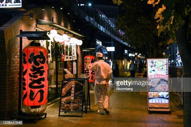 Restaurant worker walks outside an izakaya restaurant built under railway tracks in Tokyo, Japan, on Tuesday, Sept. 8, 2020. In Tokyo, the spaces...