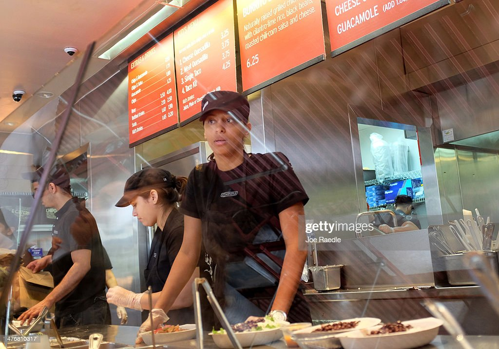Restaurant workers fill orders at a Chipotle restaurant on March 5, 2014 in Miami, Florida. The Mexican fast food chain is reported to have tossed around the idea that it would temporarily suspend sales of guacamole due to an increase in food costs.