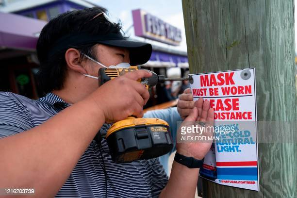 Restaurant workers install a signs informing guests that facemasks must be worn as Fish Tails bar and grill opens for in person dining, amid the...