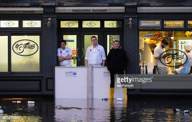 Restaurant workers look on as the street outside is flooded as a tidal surge causes flooding on January 13 2017 in Whitby United Kingdom Strong...