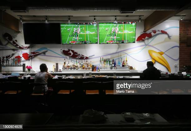 Restaurant workers sit during a break as Super Bowl LV plays on televisions in the shuttered indoor section of a restaurant on February 07, 2021 in...