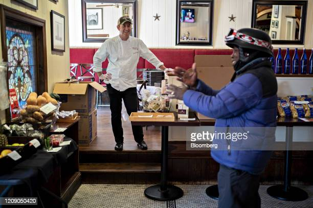 Restauranteur Geoff Tracy talks to a DoorDash Inc delivery person waiting for an order at Chef Geoff's restaurant in Washington DC US on Thursday...
