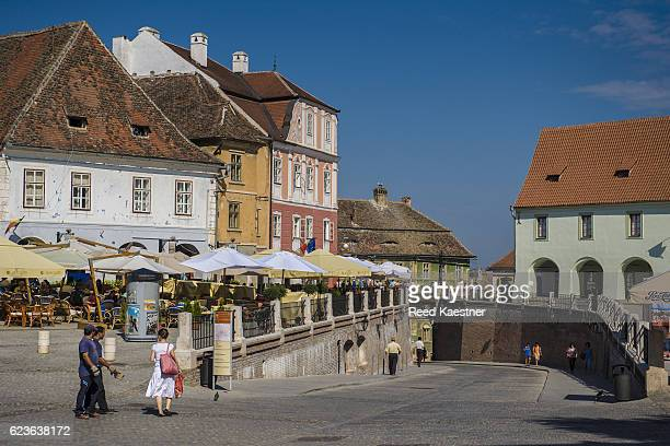 Restaurants and outdoor cafes line the Lesser Square in Sibiu, Romania