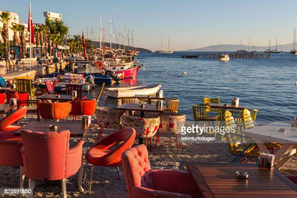 restaurants place dining tables at sandy public beach of bodrum summer town during sunset at mugla Turkey