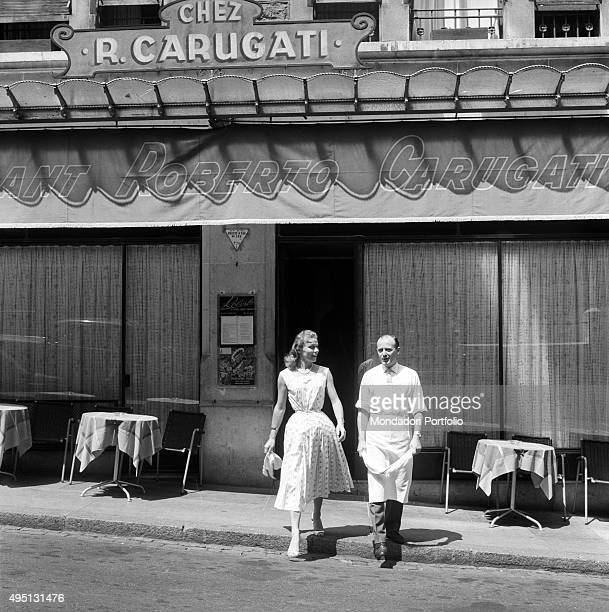 Restaurateur and chef Roberto Carugati walking beside his wife Paola in front of his restaurant in La Madeleine, Geneva, 18th July 1955. The city is...