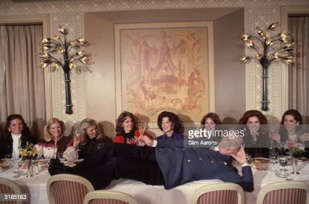 Restaurateur Sirio Maccioni laying across a table in Le Cirque in New York where a line of socialite ladies are seated From left to right Kathryn...