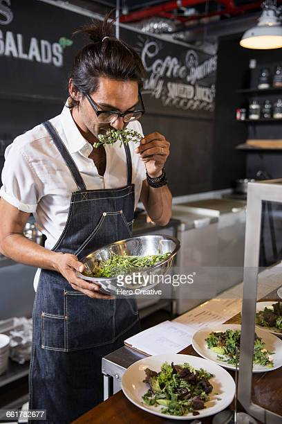 Restaurateur smelling salad leaf