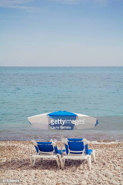 resting time - beach chairs beside the turquoise sea - calpe stock pictures, royalty-free photos & images