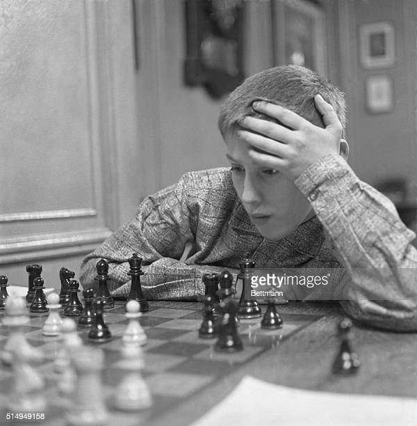 Restless hands play about the head of thirteen year old Bobby Fischer of Brooklyn as the youngest member of the Manhattan Chess Club takes part in a...