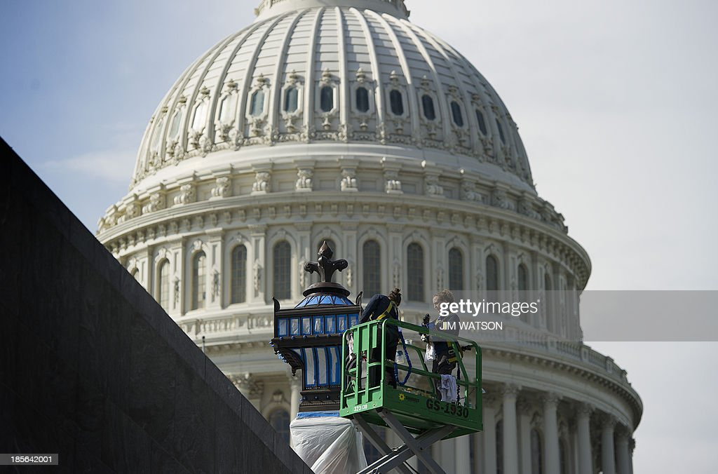 A restoration team works on a lamp outside the US Capitol in Washington, DC, October 23, 2013. For the first time since 1959-60, the Capitol dome will be subjected to complete renovations to repair nearly 1,300 cracks and other problems on the cast-iron structure. AFP PHOTO / Jim WATSON