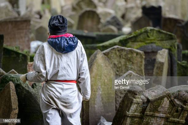 CONTENT] A restoration worker at The Jewish Cemetary in Prague preparing to undertake restoration work on one of the many many gravestones