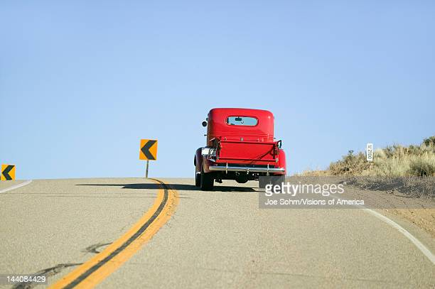 A restored bright Red Roadster hotrod pickup truck mid30's drives rural highway in Kern County near Lockwood Valley CA
