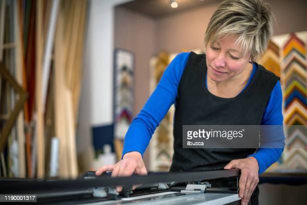 restorer and framer laboratory craftswomen: cutting frames - ilbusca foto e immagini stock