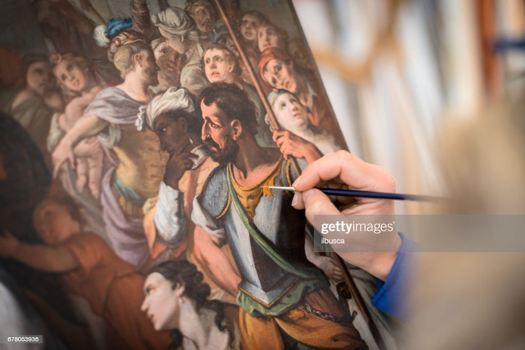 Restorer and framer laboratory craftswomen: Restoring antique religious painting canvas : Stock Photo