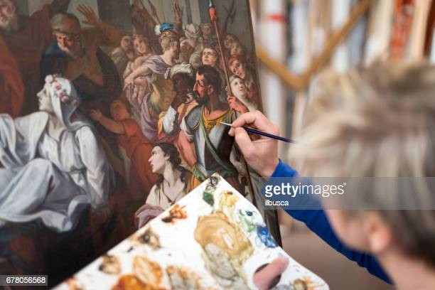 restorer and framer laboratory craftswomen: restoring antique religious painting canvas - art foto e immagini stock