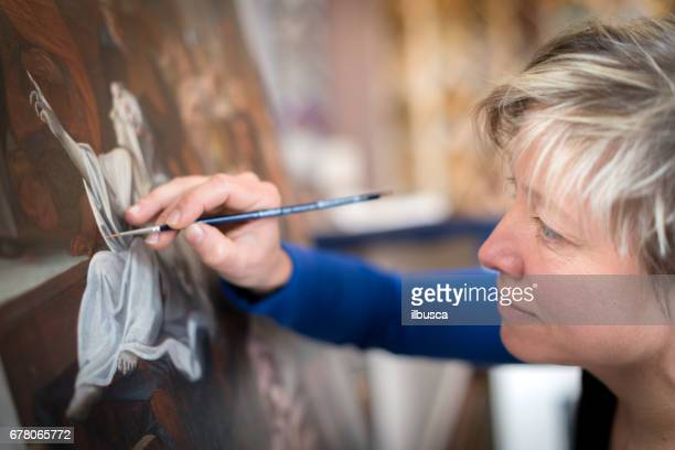 Restorer and framer laboratory craftswomen: Restoring antique religious painting canvas
