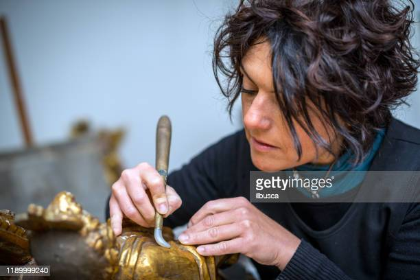 restorer and framer laboratory craftswomen: restoring antique golden angel statue - restoring stock pictures, royalty-free photos & images