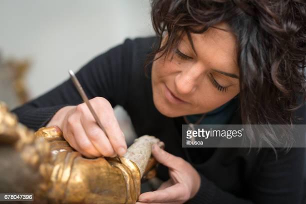Restaurator und Einrahmer Labor Handwerkerinnen: Restaurierung antiker goldener Engelsstatue
