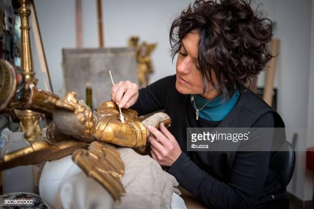 restorer and framer laboratory craftswomen: restoring antique golden angel statue - arte foto e immagini stock