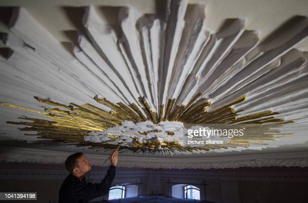Restorer Andre Baer paints the stuccoed ceiling of the palace chapel with bronze paint in Altlandsberg Germany 6 March 2015 The historic building...