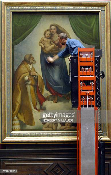 "Restorer Axel Boerner cleans the glass plate protecting Raphael's painting ""Sistine Madonna"" at Dresden's Old Masters Picture Gallery 19 January..."