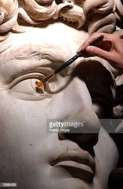 Restorer Cinzia Parnigoni cleans Michelangelo's masterpiece 'David' during restoration work at the Galleria dell'Accademia October 6 2003 in Florence...