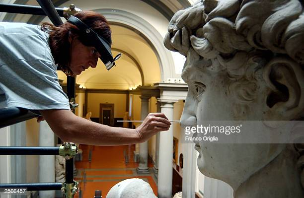 Restorer Cinzia Parnigoni cleans Michelangelo's masterpiece 'David' during restoration work at the Galleria dell'Accademia October 6 2003 in Florence...