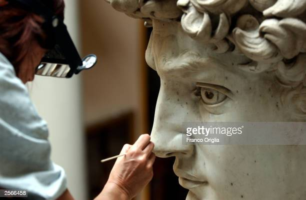 Restorer Cinzia Parnigoni cleans Michelangelo's masterpiece David during restoration work at the Galleria dell'Accademia October 6 2003 in Florence...