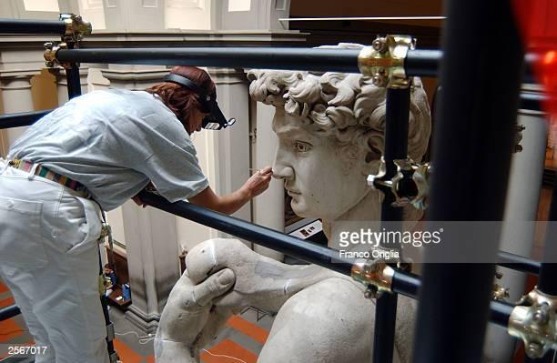 "Restorer Cinzia Parnigoni cleans Michelangelo's masterpiece ""David"" during restoration work at the Galleria dell'Accademia October 6, 2003 in..."
