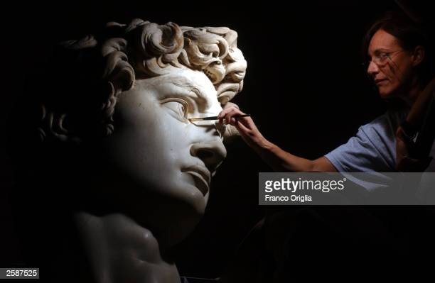Restorer Cinzia Parnigoni cleans Michelangelo''s masterpiece 'David' during restoration work at the Galleria dell''Accademia October 6 2003 in...
