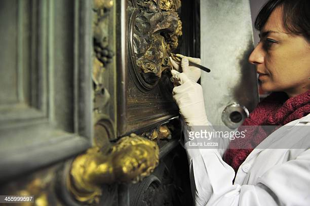A restorer cleans a panel of The North Doors Of Florence Baptistery with a scalpel in the laboratory of the Opificio delle Pietre Dure on December 12...