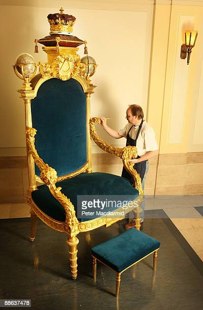 Restorer David Banham touches up the gilded arms of a ceremonial throne made for the Prince of Wales in 1790 at the Library and Museum of Freemasonry...
