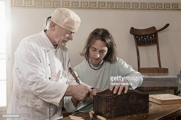 restorer master explains apprentice something on an antique bone box, bavaria, germany - negócios finanças e indústria imagens e fotografias de stock