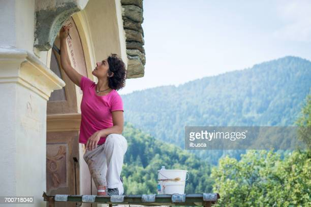 Restorer working on antique outdoor chapel fresco in Italy: Painting restoring of text