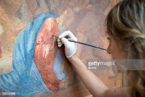 restorer working on antique outdoor chapel fresco in italy: painting restoring of religious art - art foto e immagini stock