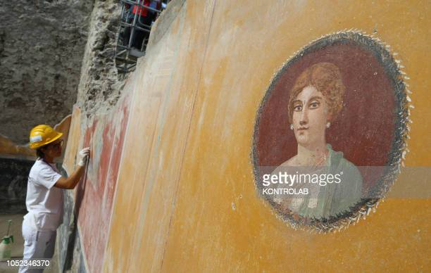 SCAVI POMPEI CAMPANIA ITALY A restorer works next to a portrait of a Patrician woman in a fresco found in the House with Garden recently discovered...