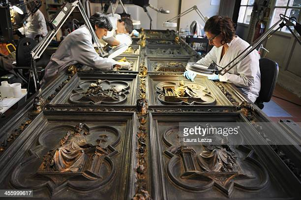 Restorers clean a panel of The North Doors Of Florence Baptistery with a scalpel in the laboratory of the Opificio delle Pietre Dure on December 12...