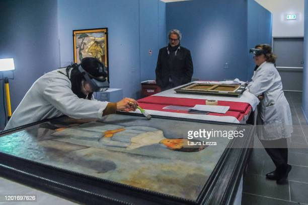 Restorers examine the condition of the painting 'Fillet en blue' by Italian artist Amedeo Modigliani during the dismantling of the exhibition...