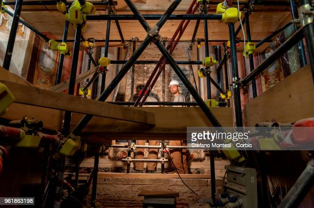 Restorers inside the Branconio chapel once an altarpiece depicting the Visitation by Raphael in the church San Silvestro of L' Aquila on May 23, 2018...