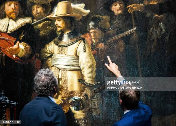 """Restorers look at Rembrandt van Rijn's world-famous masterpiece """"the Night Watch"""" in Amsterdam, on July 8, 2019. - Amsterdam's famed Rijksmuseum..."""
