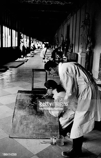 Restorers of Uffizi Gallery cleaning a painting damaged by the flood of the Arno River Florence November 1966