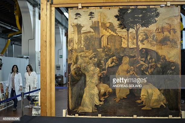 Restorers walk past the painting 'Adoration of the Magi' representing a nativity scene by Italian Renaissance master Leonardo da Vinci during its...