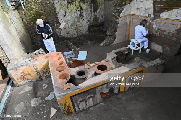 Restorers work in the new area of the 'Thermopolium' at the archaeological site of Pompeii, near Naples, on January 25, 2021. - The 'Thermopolium'...
