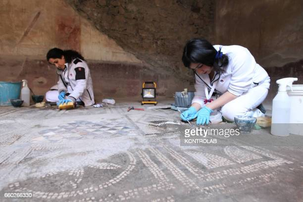 restorers work in the Wounded bear's House in the Archaeological area of Pompeii the ancient Roman town buried by the eruption of Vesuvius Volcano on...