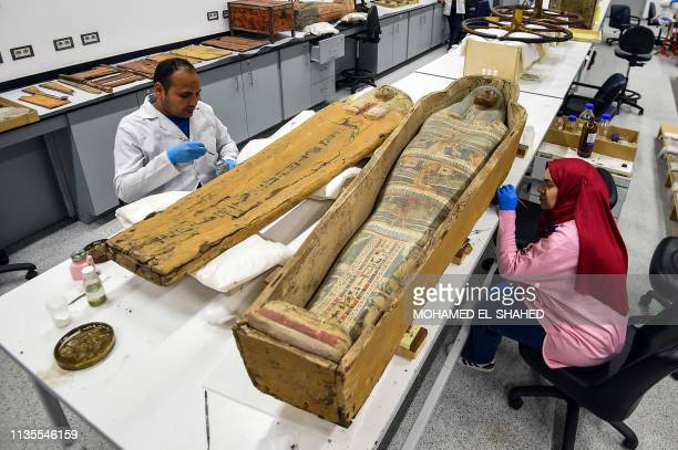 Restorers work on a sarcophagus part of the Tutankhamun collection at the restoration lab of the newly-built Grand Egyptian Museum in Giza on the...