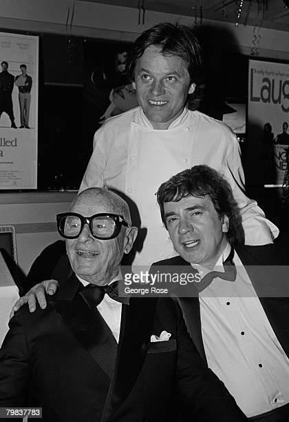 Restraunt owner Wolfgang Puck poses with Irving Swifty Lazar and Dudley Moore at the 1989 West Hollywood California Oscar Party held at Puck's Spago