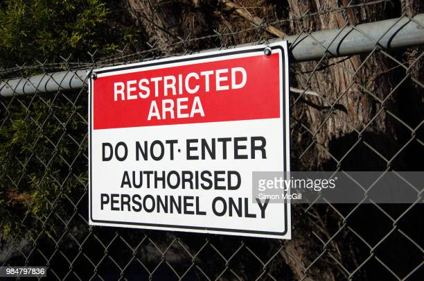 'restricted area: do not enter. authorised personnel only' sign on a chainlink fence - permission concept stock pictures, royalty-free photos & images