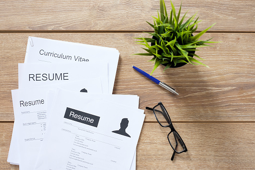 Resume applications on the desk ready to be reviewed 698820654
